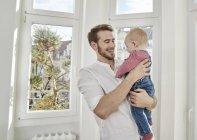 Père tient la petite fille à la fenêtre — Photo de stock