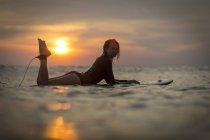Surfeur femelle dans l'océan au coucher du soleil avec ciel romantique — Photo de stock