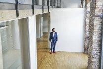 Empresário andando no escritório vazio — Fotografia de Stock