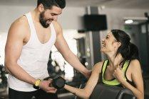 Mann Ausbildung Frau Heben von Gewichten im Fitnessstudio — Stockfoto