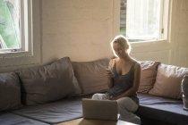 Femme blonde assise sur le canapé et utilisant un téléphone portable — Photo de stock
