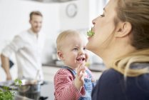 Mother with baby girl in kitchen eating herbs — Stock Photo