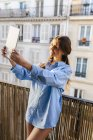 Young woman taking selfie on the digital tablet at the balcony — Stock Photo