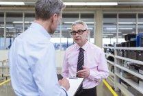 Krippen stehen und diskutieren in der Werkstatt — Stockfoto