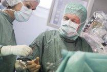 Enfermeira do bloco operatório entregar o instrumento durante uma operação — Fotografia de Stock