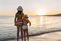 Rear view of two little sisters watching the sunset on the beach, Son Bou beach, Balearic Islands, Spain — Stock Photo