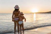 Вид сзади на двух сестричек, смотрящих на закат на пляже, пляж Сон-Боу, Балеарские острова, Испания — стоковое фото