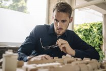 Portrait of businessman looking at architectural model — Stock Photo