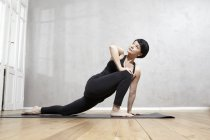 Женщина практикует йогу на деревянном полу — стоковое фото