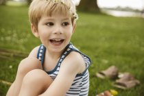 Close-up of happy blonde boy sitting on lawn in summer — Stock Photo