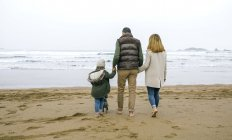 Spain, Asturias, Back view of unrecognizable family walking barefoot by the beach in winter with the sea on background — Stock Photo