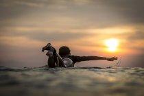 Internaute féminine dans l'océan au coucher du soleil — Photo de stock