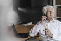 Portrait of businessman using smartphone in office — Stock Photo