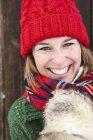 Portrait of happy woman wearing red bobble hat in winter — Stock Photo