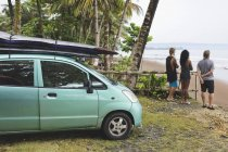 Indonesia, Java, friends standing at coast next to car with surfboards — Stock Photo