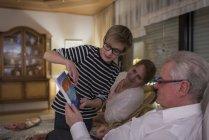 Дарування в переддень Різдва, хлопчик, показуючи представлені у бабусь і дідусів — стокове фото