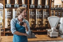 Coffee roaster holding cup of coffee in shop — Stock Photo