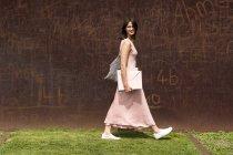 Lado del retrato de mujer joven caminando con carpeta y bolso cerca de pared marrón - foto de stock