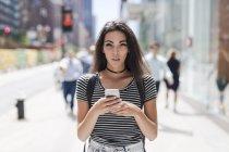 Ritratto di una giovane donna che usa lo smartphone in strada — Foto stock