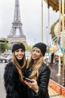 Paris, France, two best friends with a carousel and the Eiffel Tower in the background. — Stock Photo