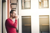 Man on balcony drinking coffee — Stock Photo