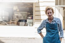 Portrait of confident coffee roaster in front of coffee shop — Stock Photo
