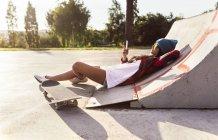 Fille de skateur Gijn, Asturias, Espagne, envoyer des messages avec son smartphone en skatepark — Photo de stock