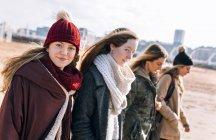 Quattro giovani donne che passeggiano in spiaggia in inverno — Foto stock