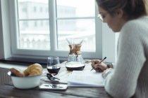 Jeune femme travaillant à table à la maison et écrire quelque chose — Photo de stock