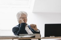 Smiling senior businessman on the phone in office — Stock Photo