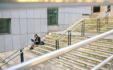 Бизнесмен, сидящая на лестнице и пользующаяся ноутбуком — стоковое фото