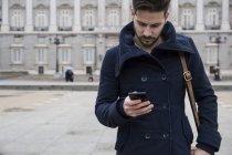 Uomo con cappotto e borsa usando il telefono — Foto stock