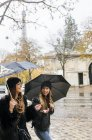 Paris, France, two female tourists walking in the city under the rain with the Eiffel Tower in the background. — Stock Photo