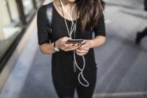 Retrato cortado de jovem mulher asiática usando smartphone na rua — Fotografia de Stock