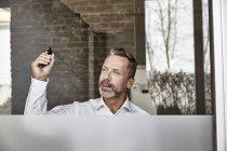 Businessman drawing on glass pane — Stock Photo