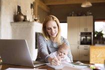 Mère avec bébé utilisant un ordinateur portable et prenant des notes à la maison — Photo de stock