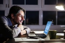 Smiling man working late in office with laptop — Stock Photo