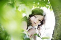 Ragazza accovacciata dietro l'albero, guardando la fotocamera — Foto stock