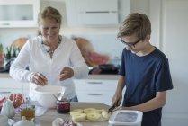 Enkel helfen Großmutter in der Küche — Stockfoto