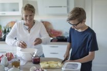 Grandson helping grandmother in kitchen — Stock Photo