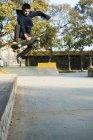 Парень-скейтбордист играет на скейтборде, прыгая с трамплина в скейт-парке — стоковое фото