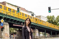 Portrait of young woman standing at street with train bridge on background — Stock Photo