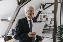 Portrait of smiling businessman holding document in office — Stock Photo