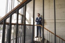 Retrato de um empresário sorridente em pé na escadaria — Fotografia de Stock