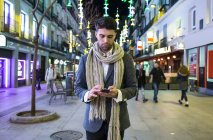Man using cell phone in city at night — Stock Photo