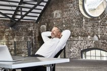 Businessman sitting at table in loft — Stock Photo