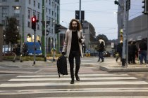 Man with bag crossing street — Stock Photo