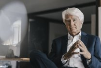Portrait of senior businessman sitting in office — Stock Photo