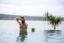Индонезия, остров Ломбок, женщина стоит в бесконечном бассейне — стоковое фото