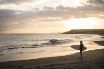 Vista distante de menino adolescente carregando a prancha de surf na praia ao pôr do sol — Fotografia de Stock